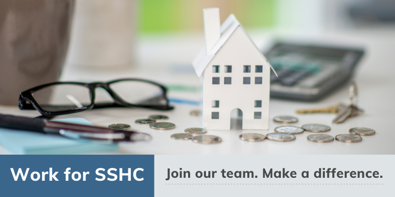 Work for SSHC. Join our team. Make a Difference. Image of a work desk with a small house, calculator, and change